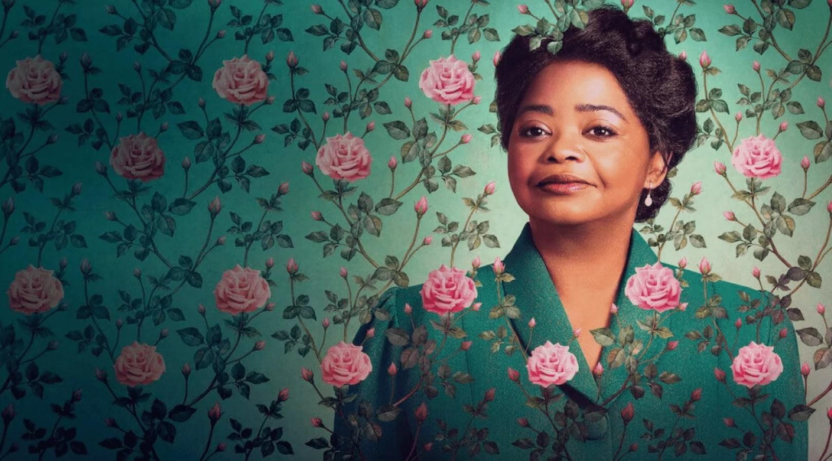 Imagem da série Madam C.J Wlaker, mostra uma mulher negra, de cabelos presos, usando uma roupa verde, em fundo verde com flores rosas.