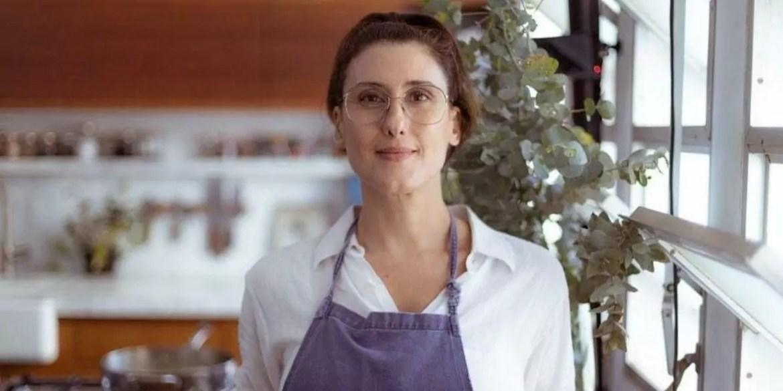 Paola Carosella posada em sua cozinha olhando para frente