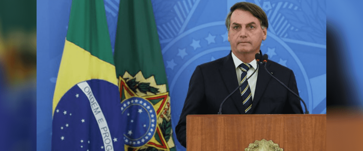 Conheça a lei de negociação de dívidas das micro empresas: Jair Bolsonaro aparece em púlpito à frente de fundo azul com o brasão Federal