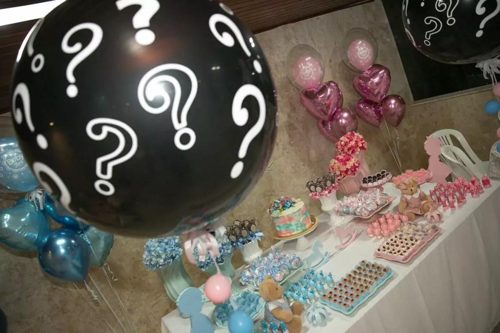 Detalhe de balão preto com pontos de interrogação que será estourado e mostrará o sexo da criança nas cores azul ou rosa