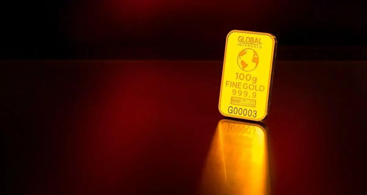 barra de ouro brilhando com fundo vermelho escuro