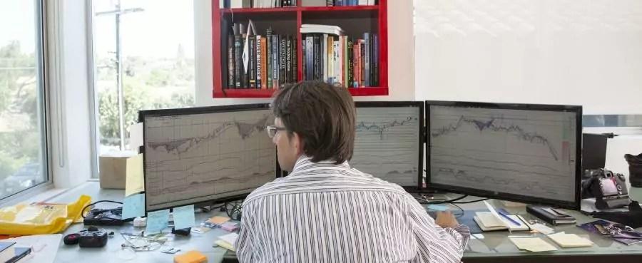 investidor acompanhando três telas de computadores com gráficos de cotação