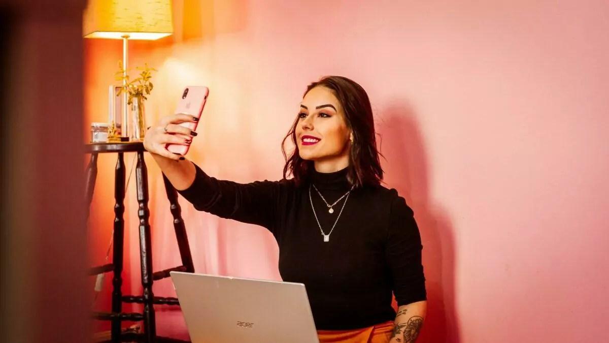 Imagem de mulher com notebook sobre o colo, segurando um celular com a mão direita e tirando uma selfie.