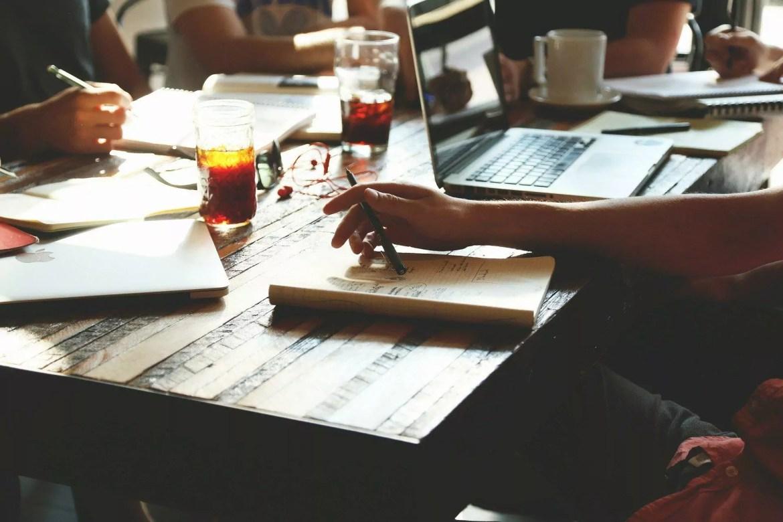 mesa com cadernos, um notebook, copos e com pessoas em volta conversando.