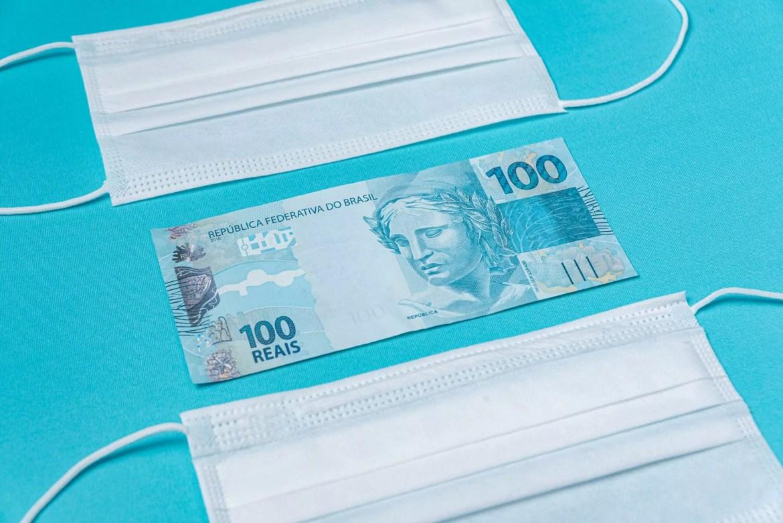 Nota de R$ 100 entre duas máscaras
