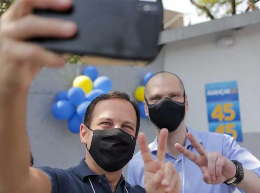 Foto mostra João Dória e Bruno Covas tirando uma selfie