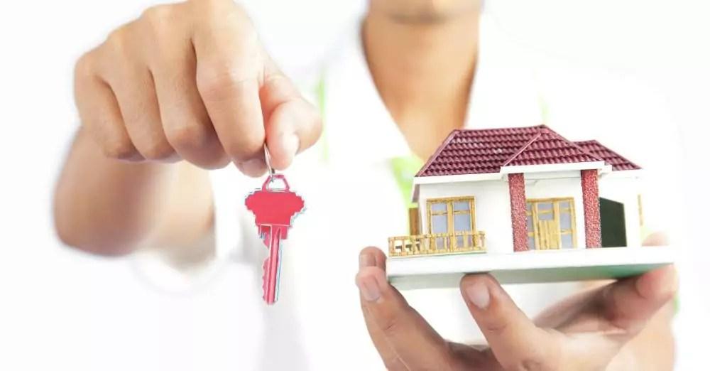 pessoa segurando chave e miniatura de casa