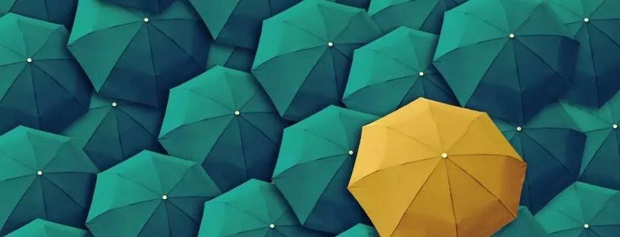 guarda-chuva amarelo aberto no meio de vários azuis