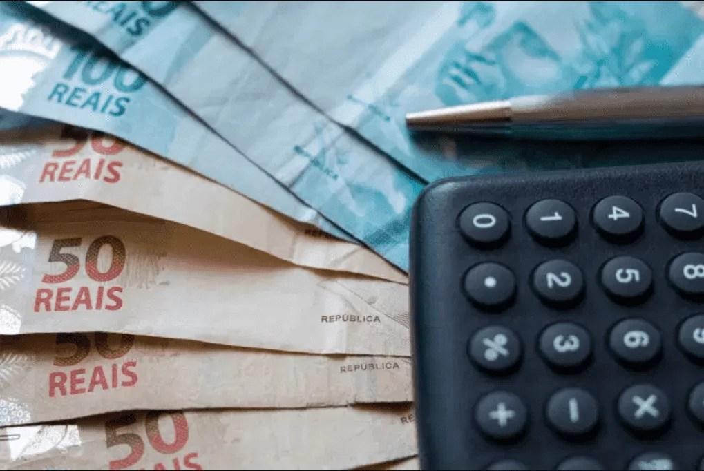 Foto mostra uma calculadora em cima de notas de dinheiro.