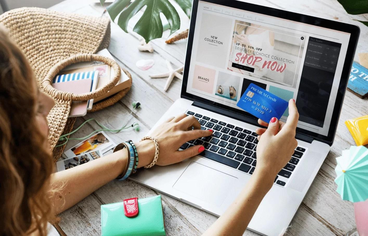 Foto mostra mulher em frente a um computador com cartão na mão