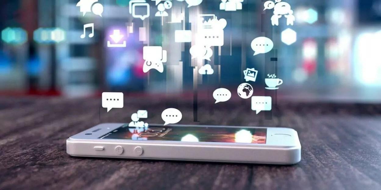 celular deitado na mesa com ícones flutuantes de redes sociais