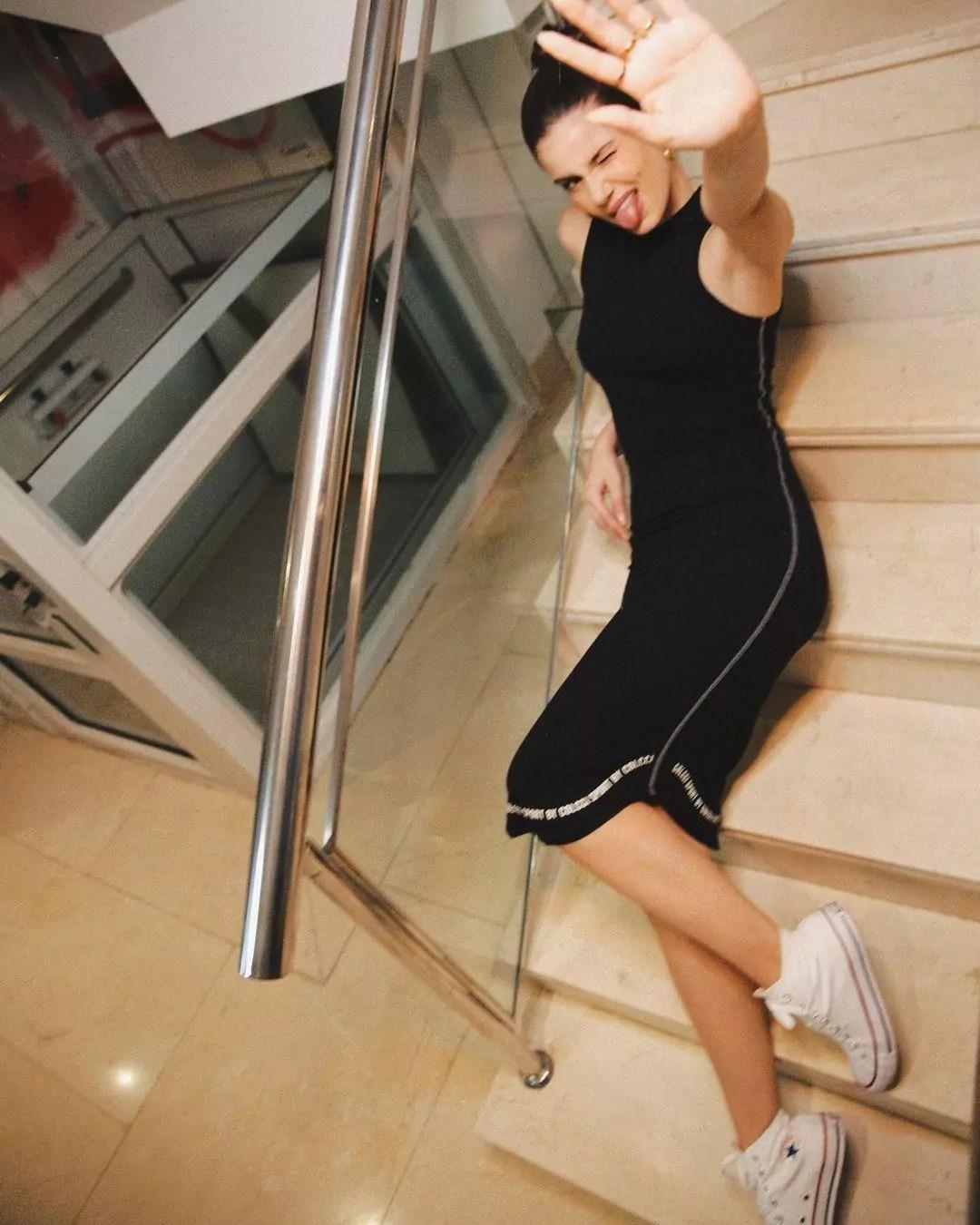 Imagem mostra Camila Queiroz com vestido preto e tênis Converse All Star