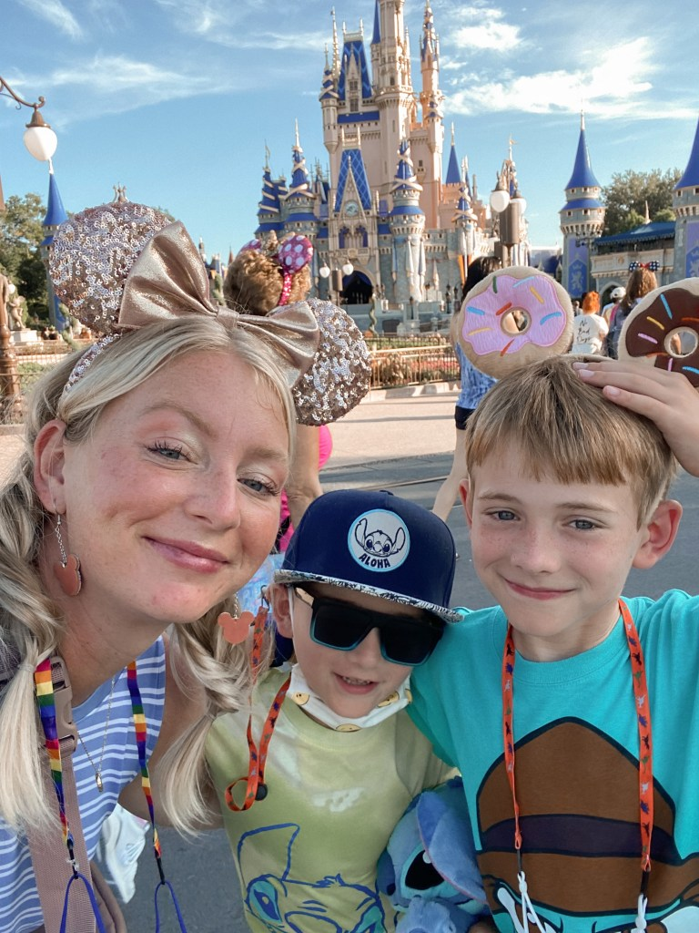 mother and son selfie in front of disney world castle
