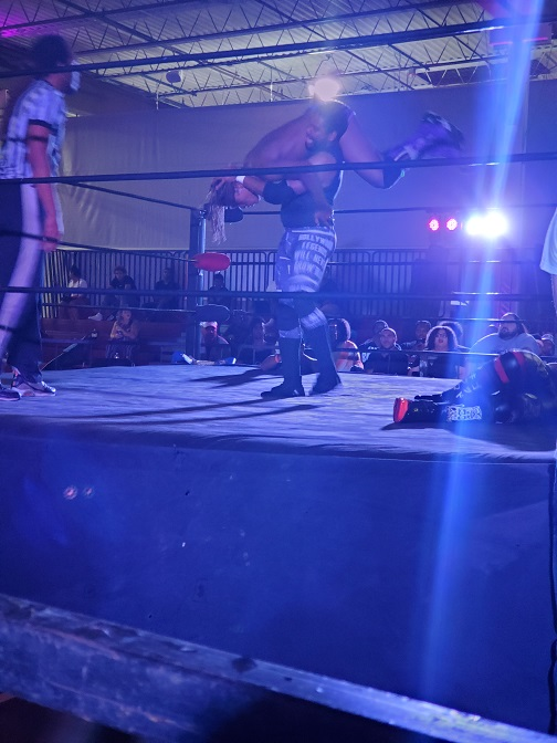 A man slams another man in the wrestling ring