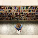 A student reads a book in a bookstore, surrounded by colourful books