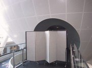 An accordion room divider blocks the entrance to a history exhibit
