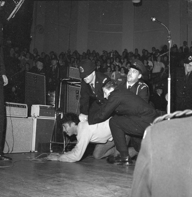 A fan is restrained during the Beatles' concert at the Wellington Town Hall, June 24, 1964