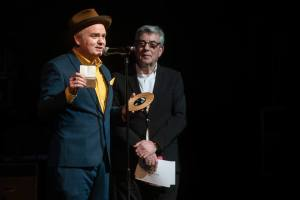 Dean Owens (in teal suit, hat and yellow shirt, on stage, being presented with Americanafest UK Song of the Year Award 2019 by Graham Gouldman (10CC)