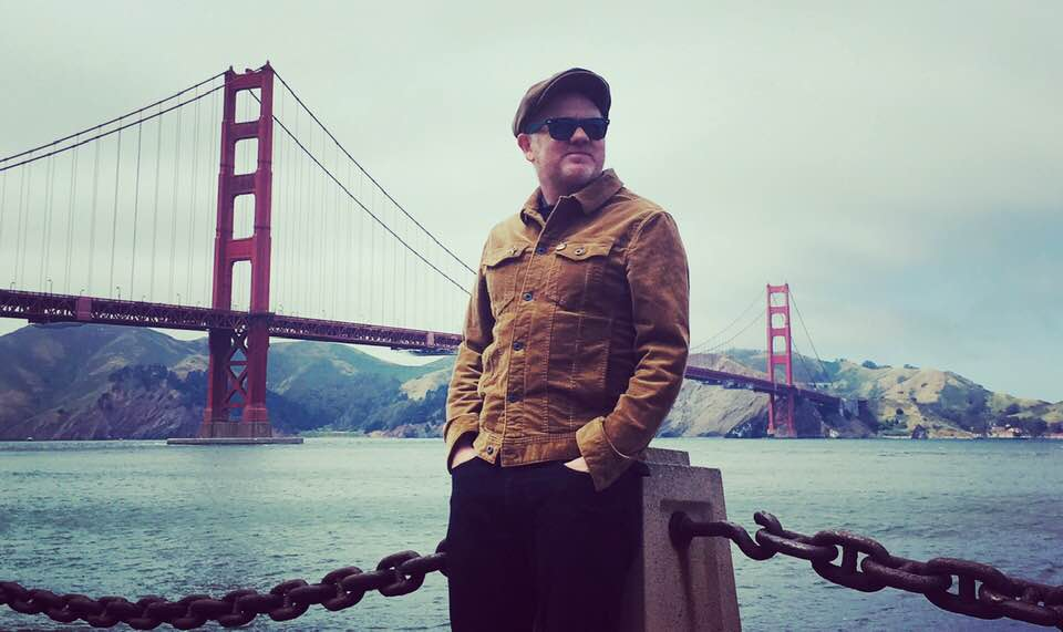 Dean Owens (in sunglasses, cap and brown jacket, leaning on a post with the Golden Gate Bridge (San Francisco) behindwith