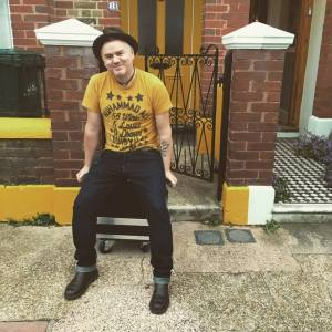 Dean, in yellow Muhammad Ali T Shirt, sitting on a flight case in front of similarly coloured house in Brighton