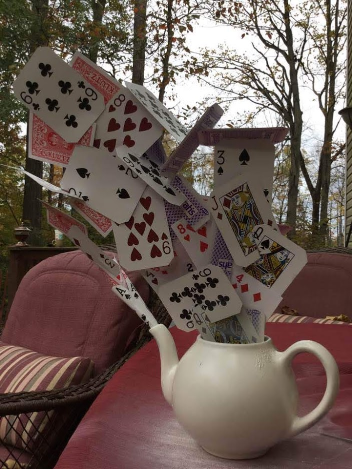 """Deck of cards """"exploding"""" out of tea pot"""