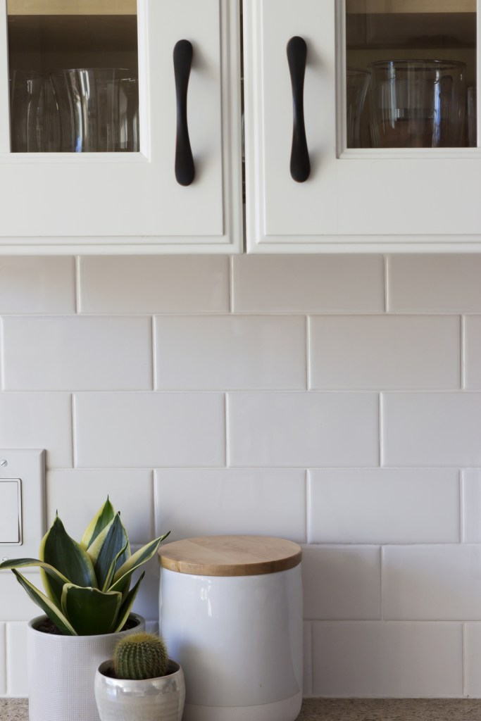 All white kitchen cabinet with dark handles, white subway tile and white counter top decorations.