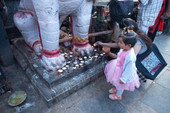 Candles are offered in front of the statue