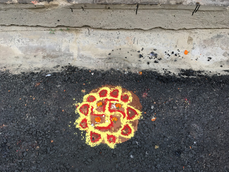 A colorful Rangoli drawn on the street in front of a store in Thamel