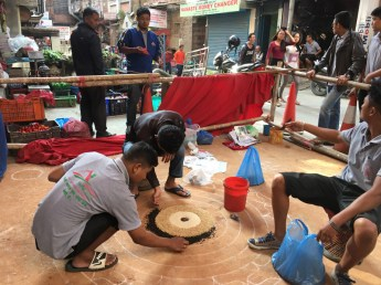 People are making a big rangoli at the corner of a street in Thamel.