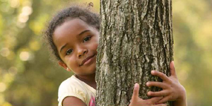Little girl holding onto a tree