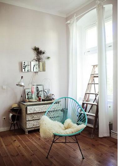 Touche de couleur dans salon gris avec un fauteuil vert menthe