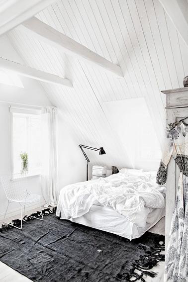 Une chambre sous combles avec un plafond en lambris blanc