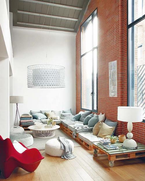 Muebles con palets reciclados con los que se componen salones de estilo industrial.