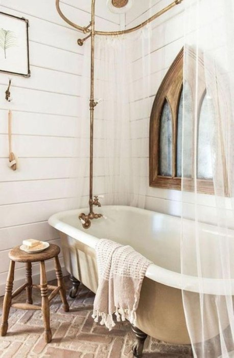 Bañeras con patas con modernas griferías que imitan las antiguas en baños vintage.