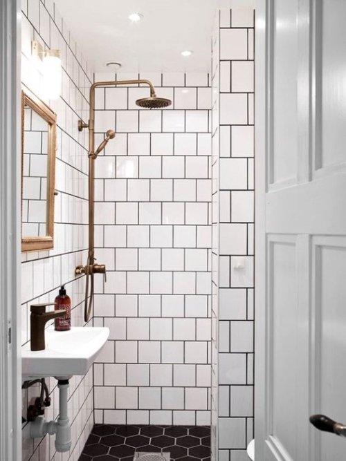 Azulejos estilo metro y suelo de hexágonos definen el cuarto de baño de estilo industrial.
