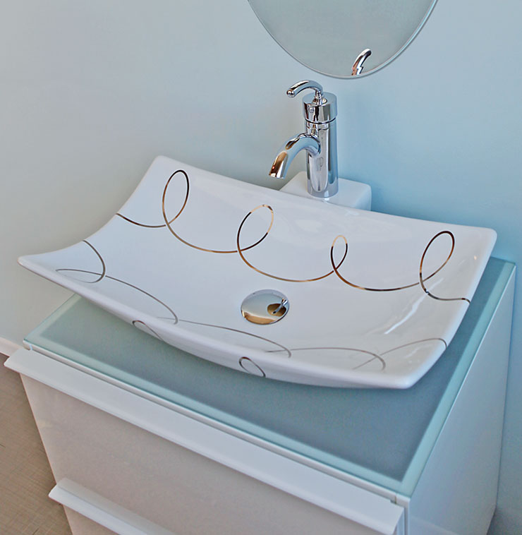 Blue spa bath with Loose Loops design in silver on a white vessel sink