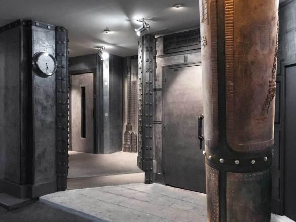 Décoration d'un hall d'immeuble avec des murs métal en trompe l'oeil et des IPN style Eiffel