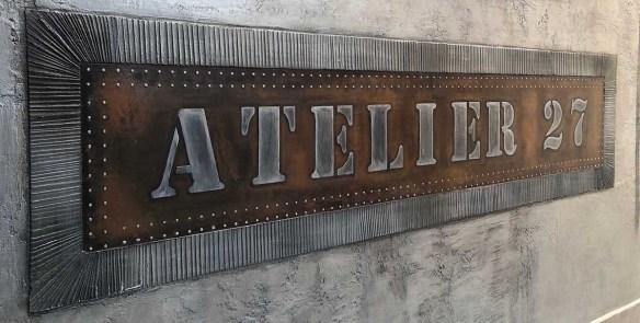 enseigne style industriel en incrustation béton sur mur métal