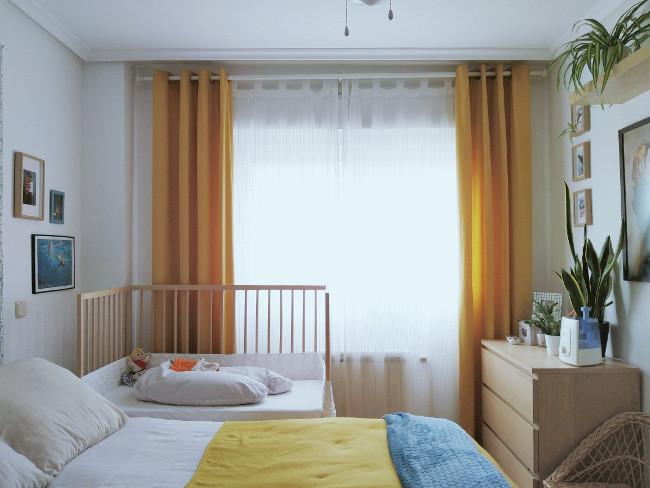 dormitorio de matrimonio con cuna de colecho junto a la ventana