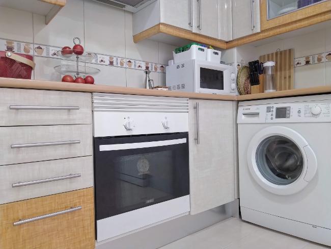 cocina donde se ven el horno, el microondas y la lavadora