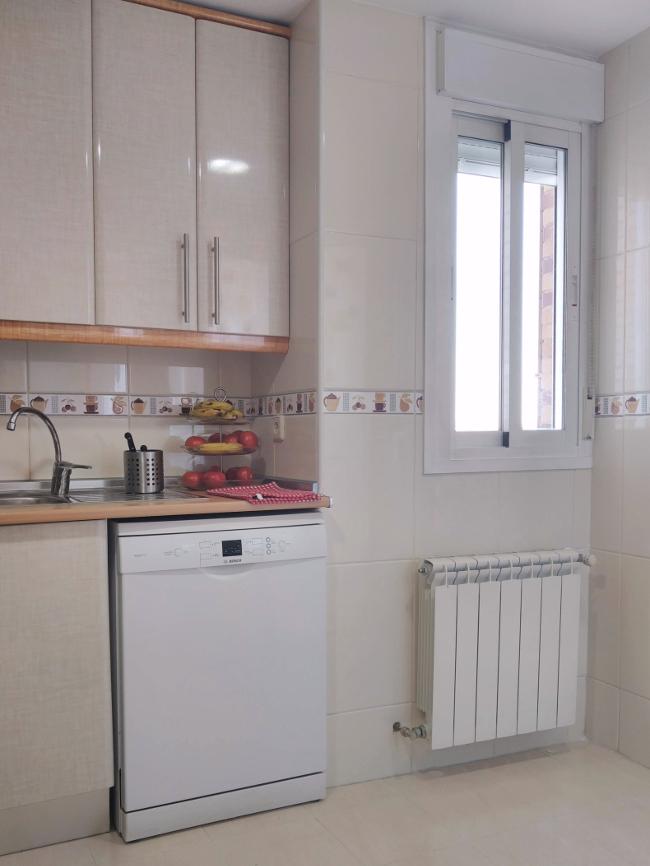 la ventana de la cocina sin cortina - está rodeada de azulejos y pegada a la esquina
