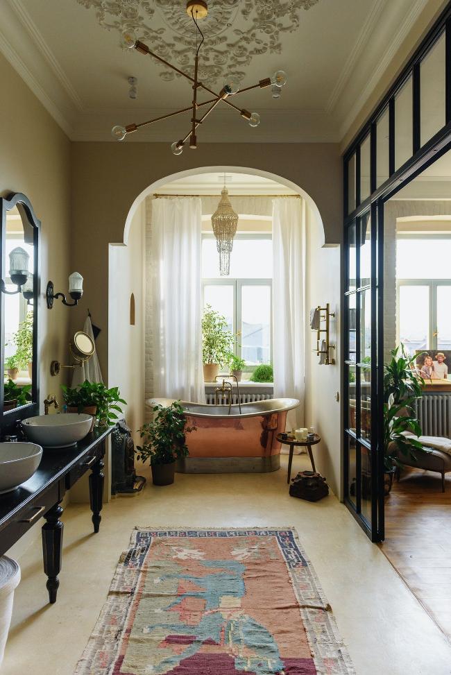 cuarto de baño con bañera de latón y lavabos de estilo vintage