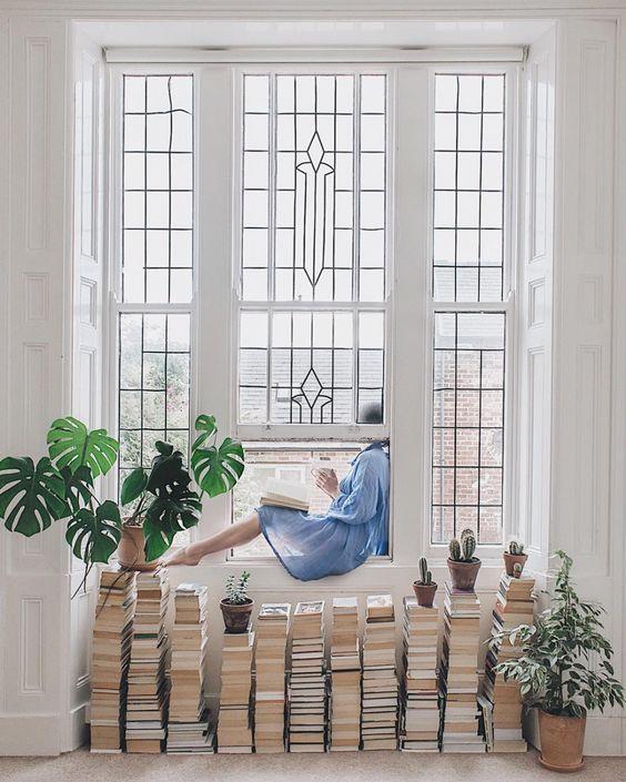 pilas de libros bajo la ventana