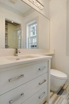 bathrooms - brown beige ivory cream glass tiles floors modern white three drawer bathroom vanity chrome pulls hardware faucet fixture mirror modern light fixture white walls paint color