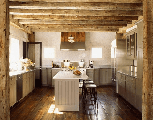 kitchens - rustic kitchen exposed wood beams white kitchen island gray kitchen cabinets stools glass front kitchen cabinets pendant island lights rustic wood floors