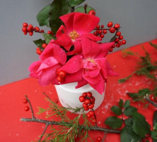 Un centre de table de Noël avec des branches de houx et des fleurs