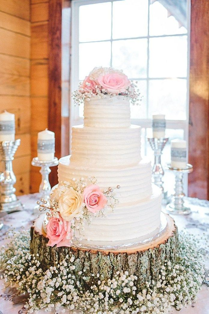 white buttercream wedding cake with tree stupm and baby's breath flowers