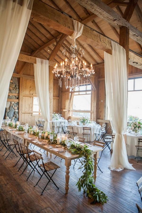Barn wedding reception desk with draping fabric and greenery table runner