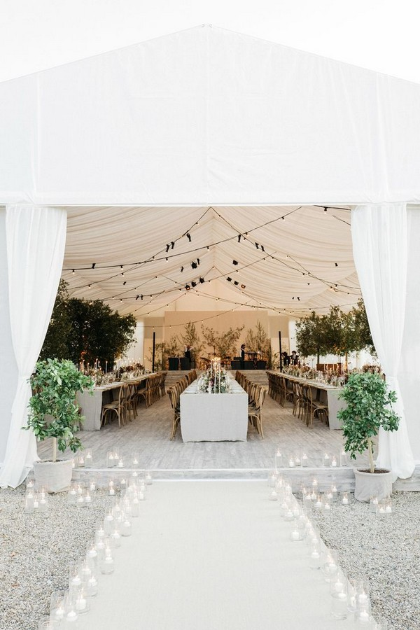 Glass jars filled with glowing white candles lined the walkway leading to the tent