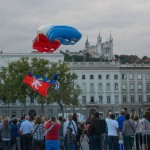 Arrivée d'un parachutiste, avec un drapeau de la ville de Lyon, de l'équipe de France militaire et de l'équipe de présentation et de compétition de l'armée de l'air sur la la place Bellecour de Lyon pour les commémoration de la libération de la ville de Lyon